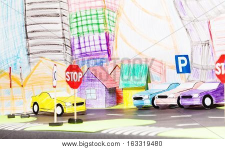 Picture of road traffic in the toy city with signs, parking, paper houses and cars models