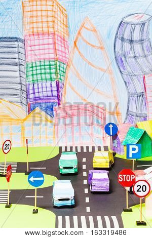 Road traffic at the toy city with signs, parking, crossings and colored paper cars