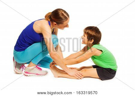 Young mother teaching her kid boy stretching leg muscles before training, isolated on white