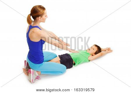 Five years old boy making gymnastics laying on the floor with female trainer, isolated on white