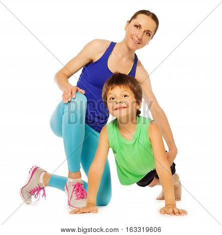 Cute kid boy doing pushing ups with his mother, isolated on white