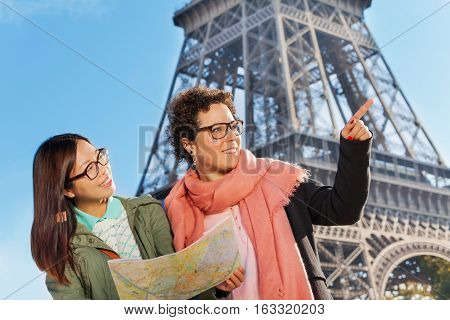 Close-up portrait of two young women searching right way travelling in Paris