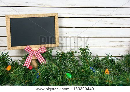 black chalkboard with gingham bow in Christmas pine and colorful lights