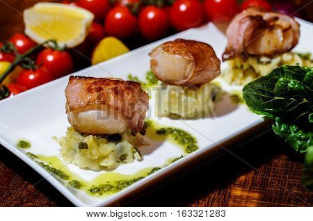 Seared scallops wrapped in panchetta, dill mouli mash and lemon curd drizzle