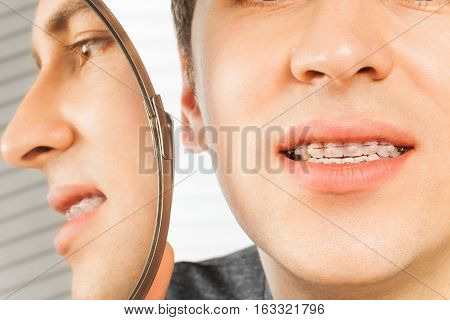 Patient with dental braces looking in the mirror in dentist's office