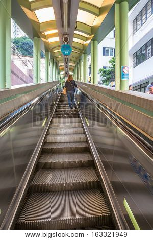 Hong Kong, China - December 4, 2016: People use the Central Mid Levels escalator in Hong Kong, the longest outdoor covered escalator system in the world, to move from Central to Western District.