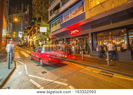 Hong Kong, China - December 10, 2016: Typical red taxis on Elgin Street by night, popular road Soho district in Central Hong Kong, famous for bars, restaurants, clubs and nightlife.