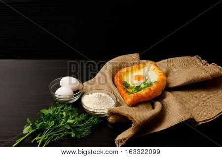 Khachapuri with eggs on sackcloth flour eggs and parsley on black table space for text