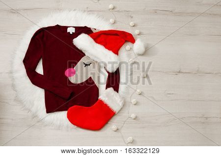 New concept sweater with deer and a santa hat stocking. Garland wood background space for text
