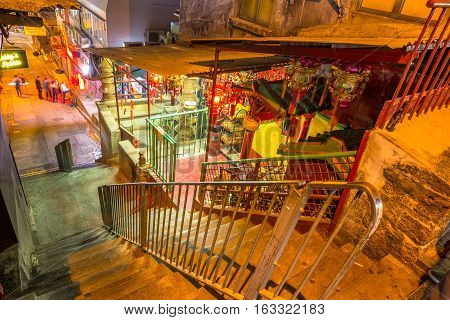 Hong Kong, China - December 10, 2016: the typical narrow streets of the tourist district of Soho by night, in Central Hong Kong, famous for bars, restaurants, clubs and nightlife.