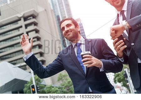 Two handsome businessmen stopping car with hand outdoors