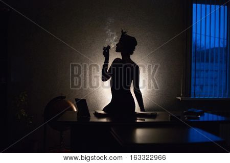 photo noir retro silhouette of a girl in front of a window with a blue light a woman smoking a cigarette in the mouthpiece a woman with a pen on head sitting on a table. globus retro