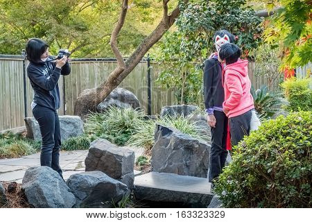 Sydney, Australia - May 22, 2016: At the popular Auburn Botanic Gardens, Japanese Zen Gardens section. Teenagers filming a scene from the popular Japanese fox legend story.