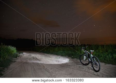 starry sky night photography astrophotography tree silhouettes big bear white mountain bike with a flashlight standing on the field