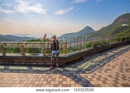 Young, smiling and fashionable tourist takes selfie on the popular free viewing terrace overlooking Victoria Peak Galleria in Hong Kong island.