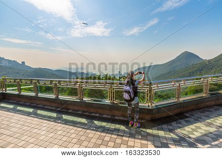 Young, smiling and fashionable tourist woman takes pictures with her smart phone on the free viewing terrace landmark overlooking Victoria Peak Galleria that on the Reservoir in Hong Kong island.
