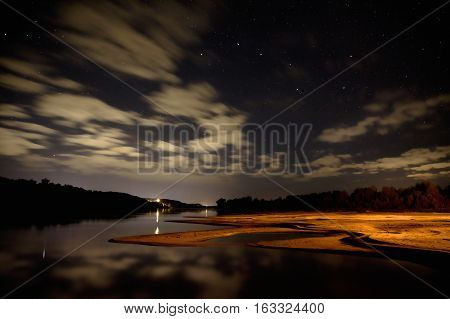 night over the river the stars and clouds in the night sky the beach is illuminated with light from the fire the Big Dipper in the sky