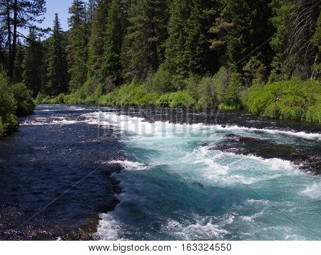 The channel and rich blue color of Wizard Falls on the Metolius River in Central Oregon on a sunny summer day.