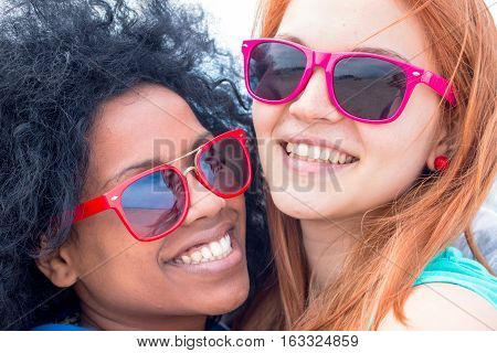 2 multi-ethnic girls best friends smiling together wearing sun glasses posing for photo