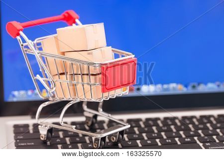 Shopping cart with cardboard boxes on laptop. E-commerce concept.