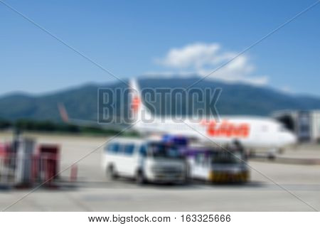 Blur abstract background plane at the airport on loading and ground service. Blurry view airplane parking . Defocused light aircraft land on runway passengers boarding.