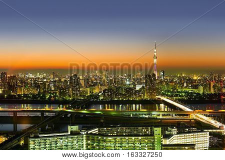 Asia Business concept for real estate and corporate construction - panoramic modern cityscape building bird eye aerial night view of skytree under neon light and beautiful dark blue sky in Tokyo Japan