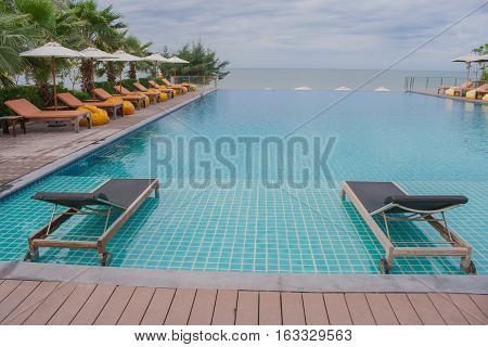 Daybed beside swimming pool in the resort.