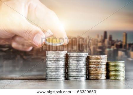 Saving money concept preset by Male hand putting money coin stack selective focus