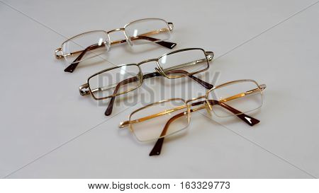 three pairs of glasses on a light background