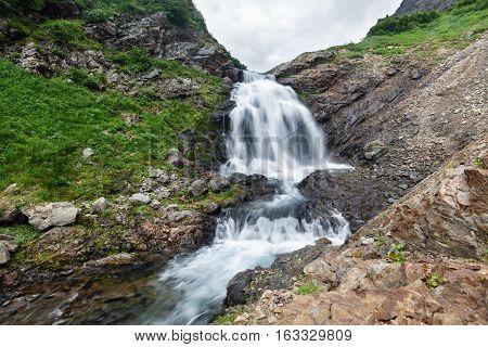 Summer landscape of Kamchatka Region: beautiful view of mountain river and waterfall in Mountain Range Vachkazhets. Kamchatka Peninsula Russian Far East Eurasia.