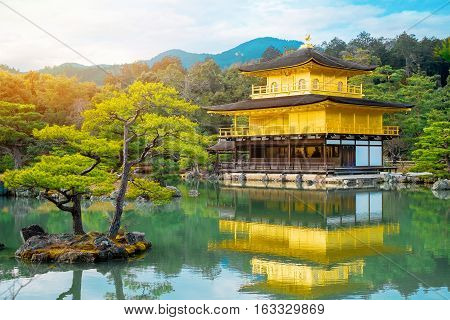 The world cultural heritage Kinkaku Ji under dramatic morning sunshine the traditional golden zen buddhist temple in Kyoto Japan