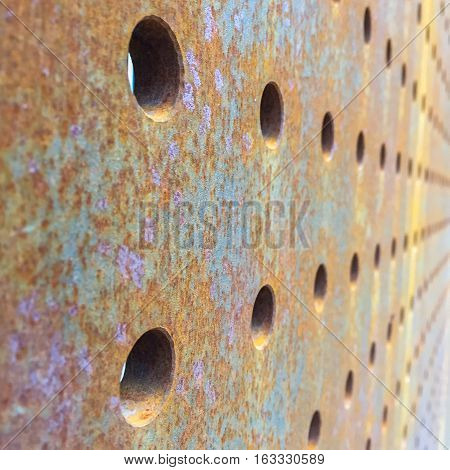 Thick Rusty Steel Plate with Lines of Holes