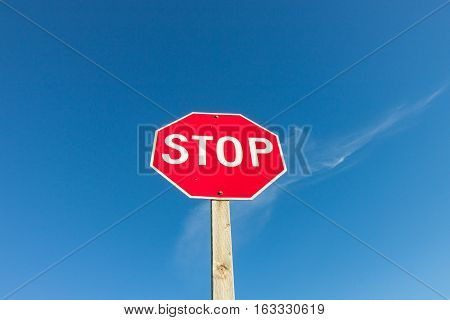 Isolated Red Stop Sign Against Blue Sky