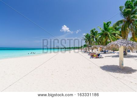 beautiful amazing gorgeous view of tropical white sand beach with people relaxing, swimming in background