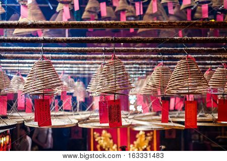 Circular incenses people pray to god for blessing in traditional old oriental chinese temple in Hong Kong(HK) (Chinese Translation on paper : wish all the best for life)