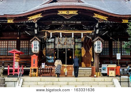People pray for blessing at famous heritage shrine in Tokyo Japan (translation of word on lantern : Kumano Shrine)