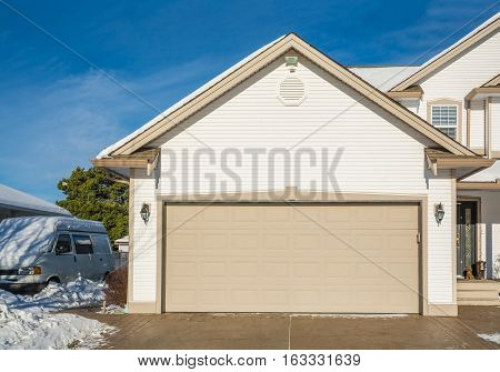 Wide garage door of luxury house with concrete driveway and RV wagon parked nearby. Residential house on winter sunny day