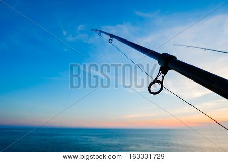 The silhouette of fishing poles under dramatic sunset and beautiful sea