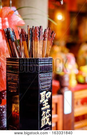 Asia culture concept image - fortune sticks in traditional temple people shake for good future(Chinese Translation on bamboo : fortune sticks)