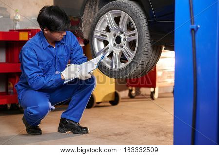 Young mechanic making list of car malfunctions