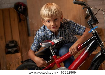 Little boy adjusting bicycle seat before riding