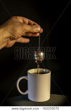 man's hand preparing tea in a bowl with infuser on background