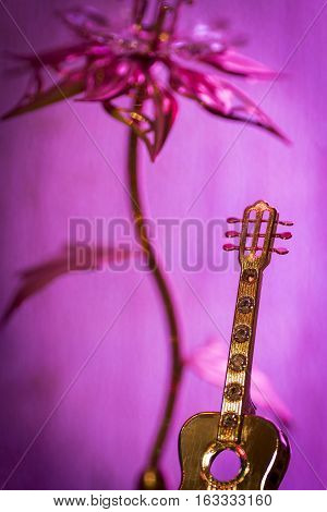 Small golden figure of classical guitars close-up as abstraction.