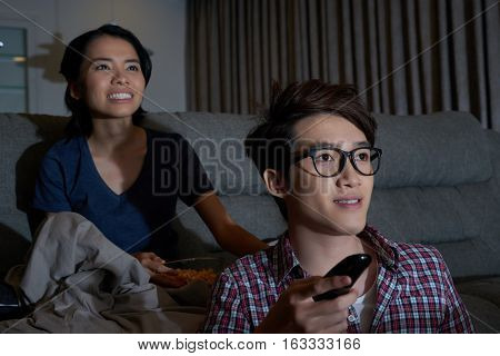 Asian couple excited to watch new episode of tv show