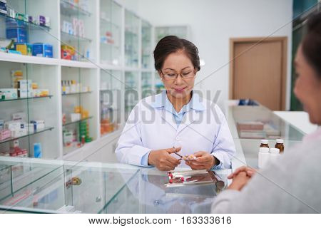 Mature Asian pharmacist selling different pills to the customer