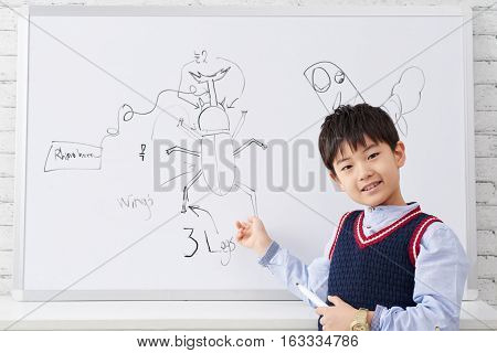 Schoolkid pointing at bug he drew on whiteboard