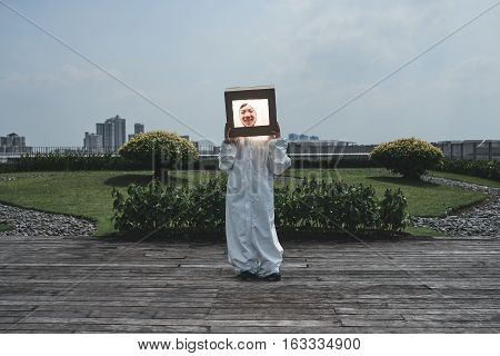 Little boy in handmade cosmonaut costume standing outdoors