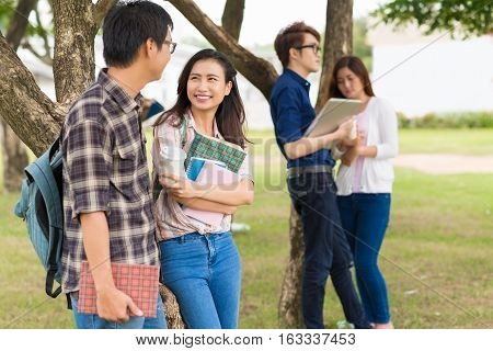 Cheeful Asian classmates discussing homework on campus
