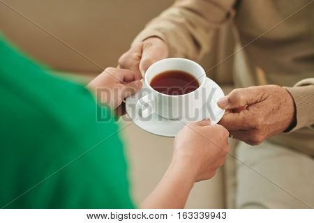 Nurse giving cup of tea to aged man, view from above