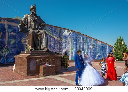 Samarkand Uzbekistan - 19 August 2016: Newlyweds at the monument to Ulugbek by August 19 2016 in Samarkand Uzbekistan.